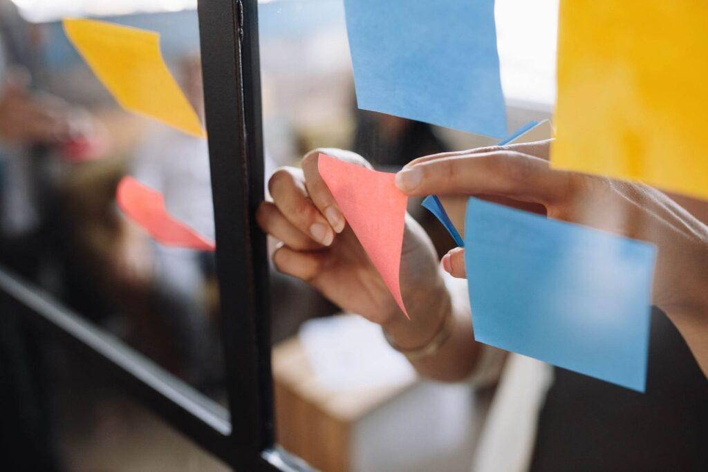 Mãos de uma mulher colando post-it no vidro do escritório.